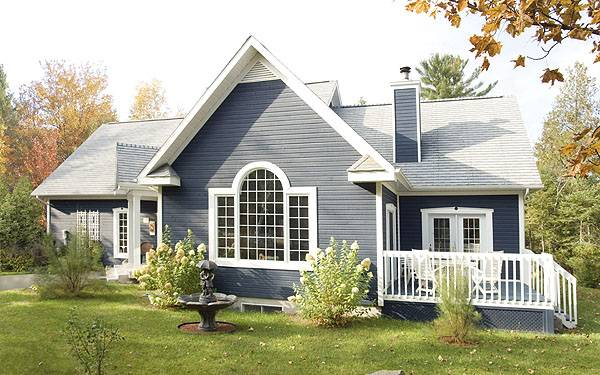 Rear exterior view with palladian window, blue chimney, and a deck framed with white railings.