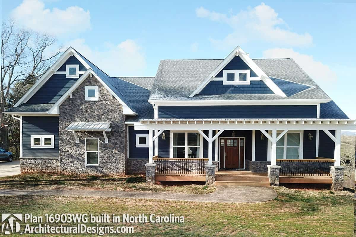 Front exterior view showing the wide covered porch and blue siding accentuated with striking stones and white trims.