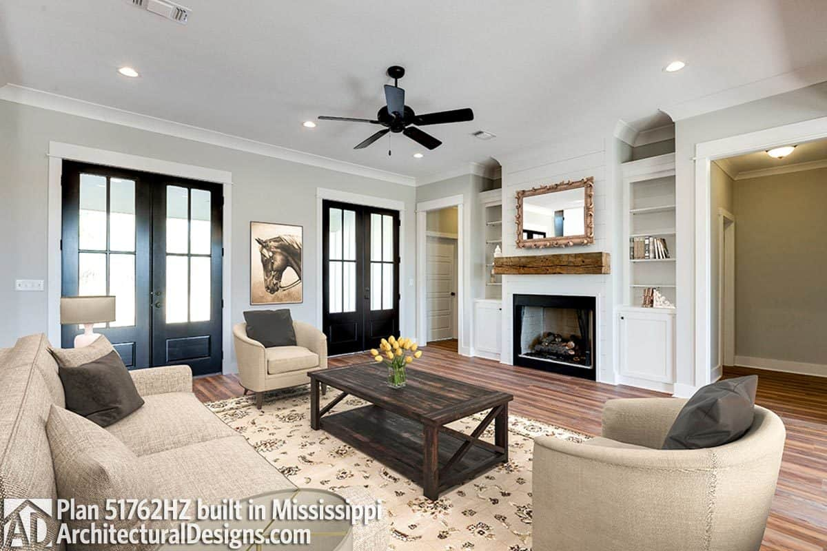 The living room has beige seats, a rustic coffee table, and a fireplace flanked by white built-ins.