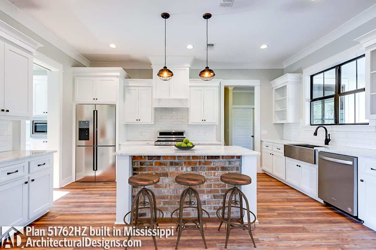 Kitchen with white cabinetry, slate appliances, subway tile backsplash, and a 3-seater island.