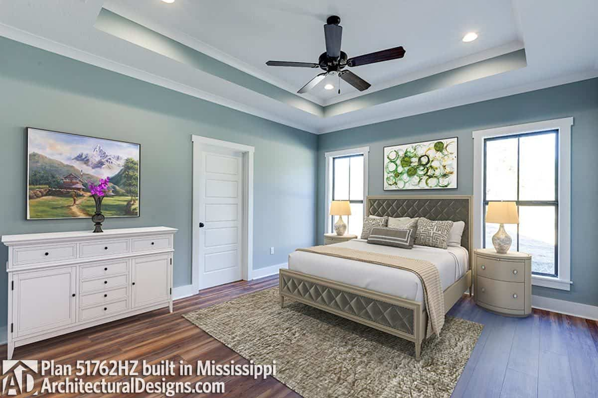 The primary bedroom has gray walls, an upholstered bed, hardwood flooring, and a tray ceiling mounted with a fan and recessed lights.