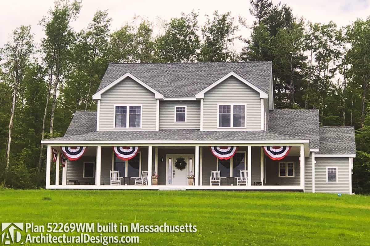 Decorative flags and a wreath placed against the white entry door adorn this two-story farmhouse.