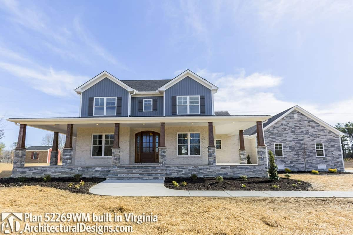 This home showcases a combination of stone and blue siding, tapered columns, and an arched entry door.