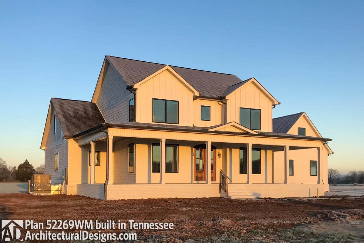 This home has board and batten siding, gable rooflines, and a wraparound porch complemented with a white stoop.