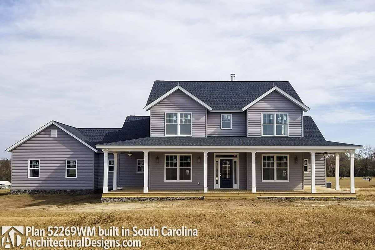 This home has a raised front porch and gray siding accentuated with white trims and framed windows.