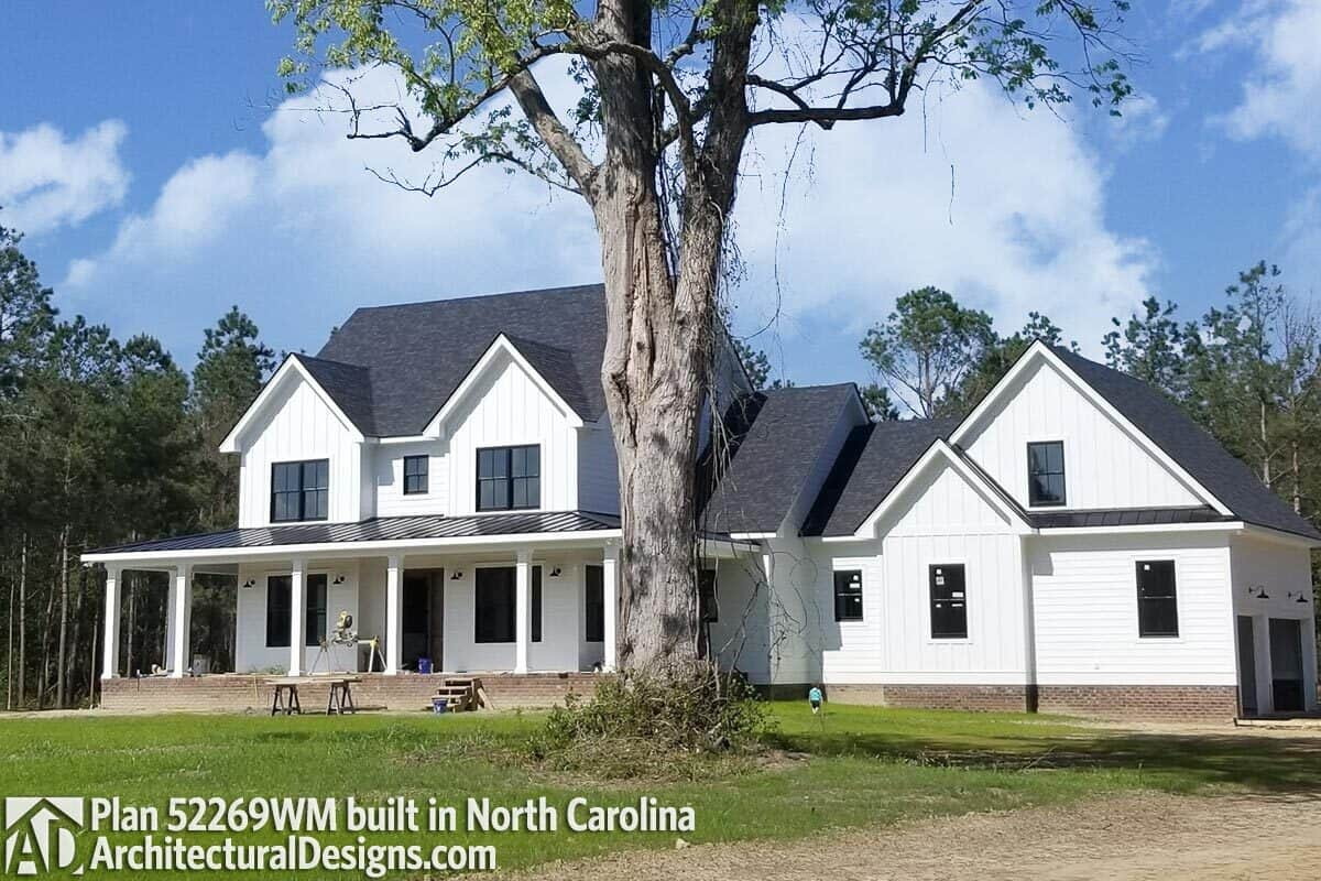This home has gable rooflines, white siding, and brick bases.