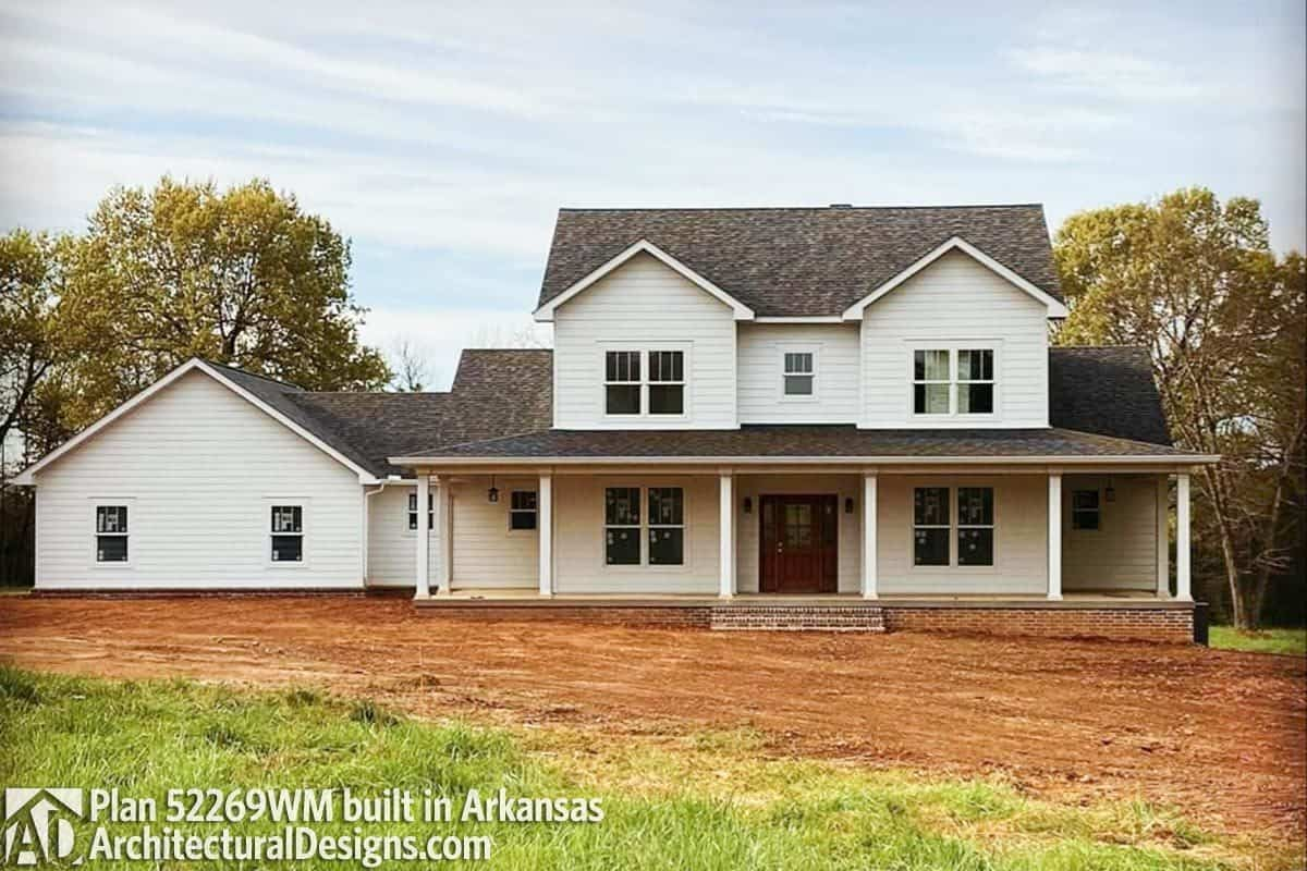 This home is built in a sloped lot showcasing a raised front porch and side-entry garage.