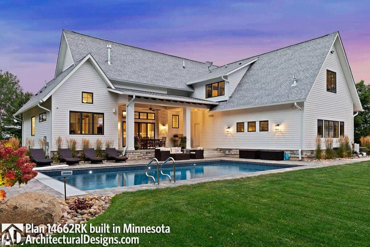 Wicker seats and loungers complement the pool while a summer kitchen and outdoor dining fill the covered porch.