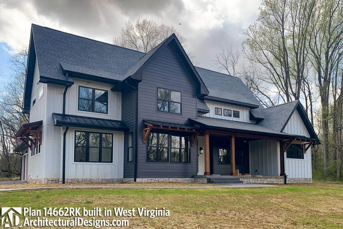This home has a combination of gray and charcoal siding, gable rooflines, and an inviting front porch with a stoop.