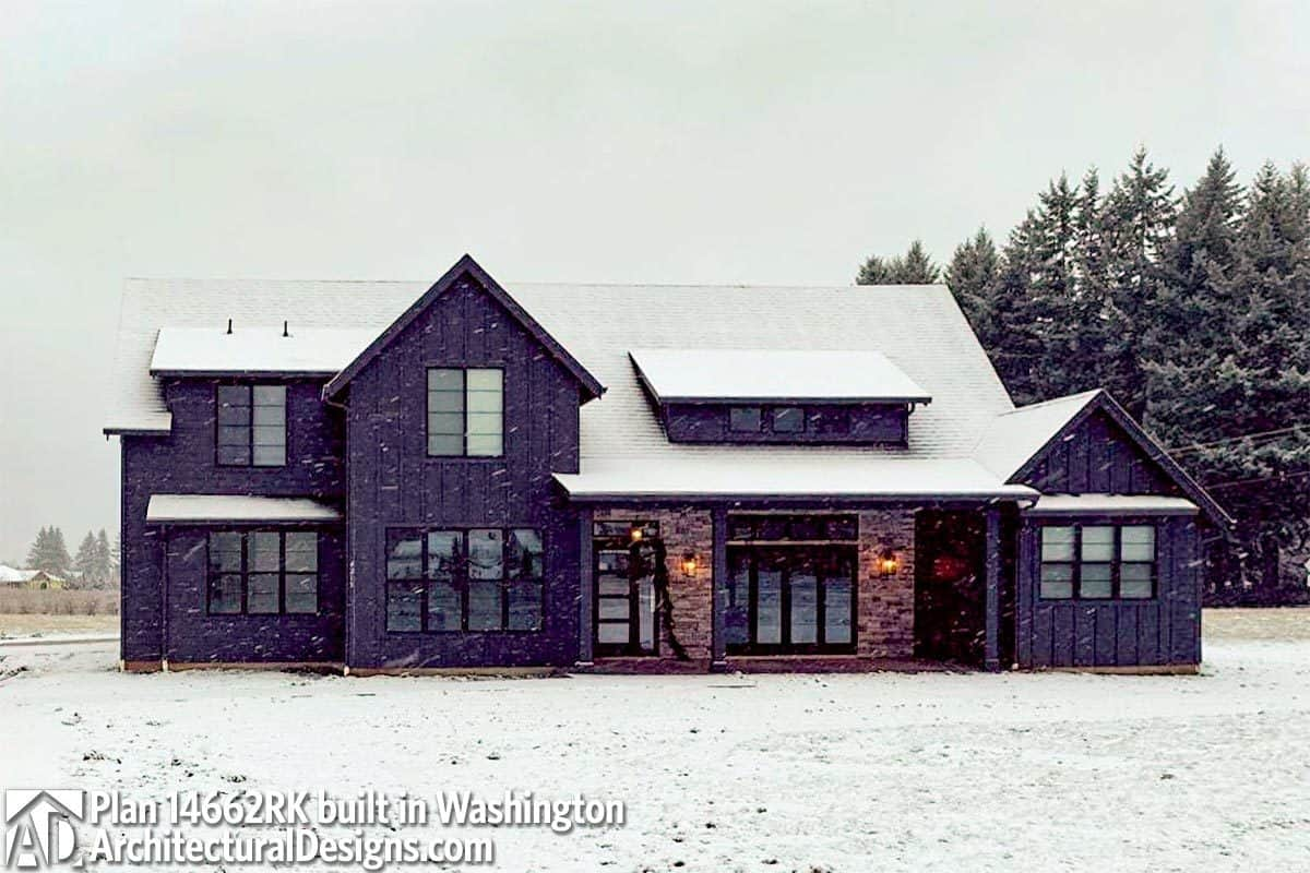 The home's dark exterior accentuated with bricks stands out against the snow.