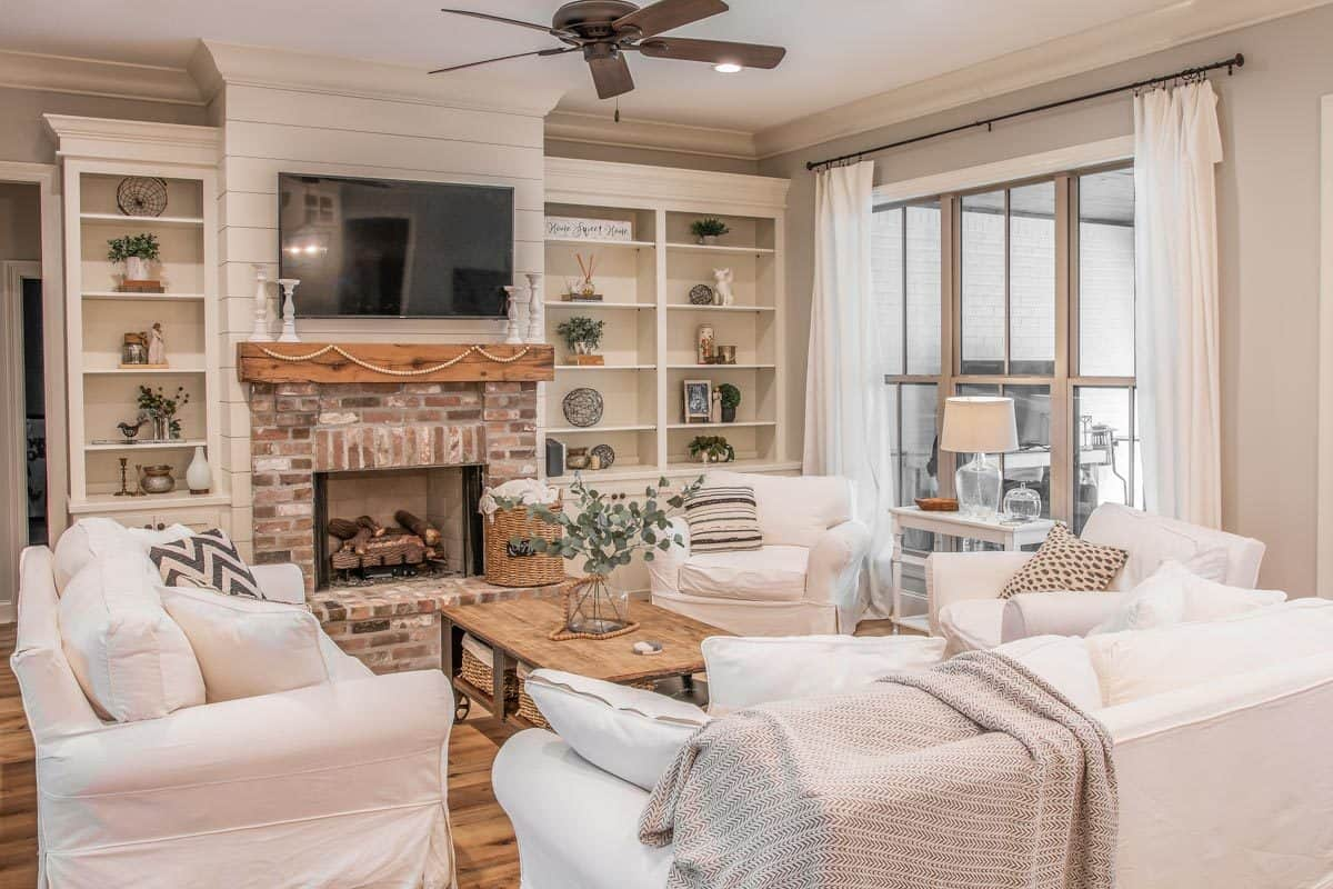 The living room has white skirted seats, built-in cabinets, and a brick fireplace with a TV on top.