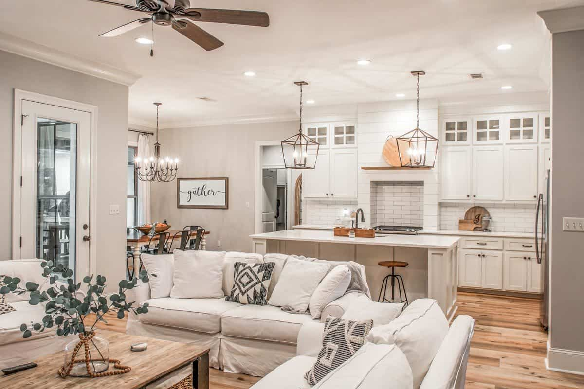 Sitting behind the living area is the kitchen that's brightened by recessed ceiling lights and a pair of caged chandeliers.