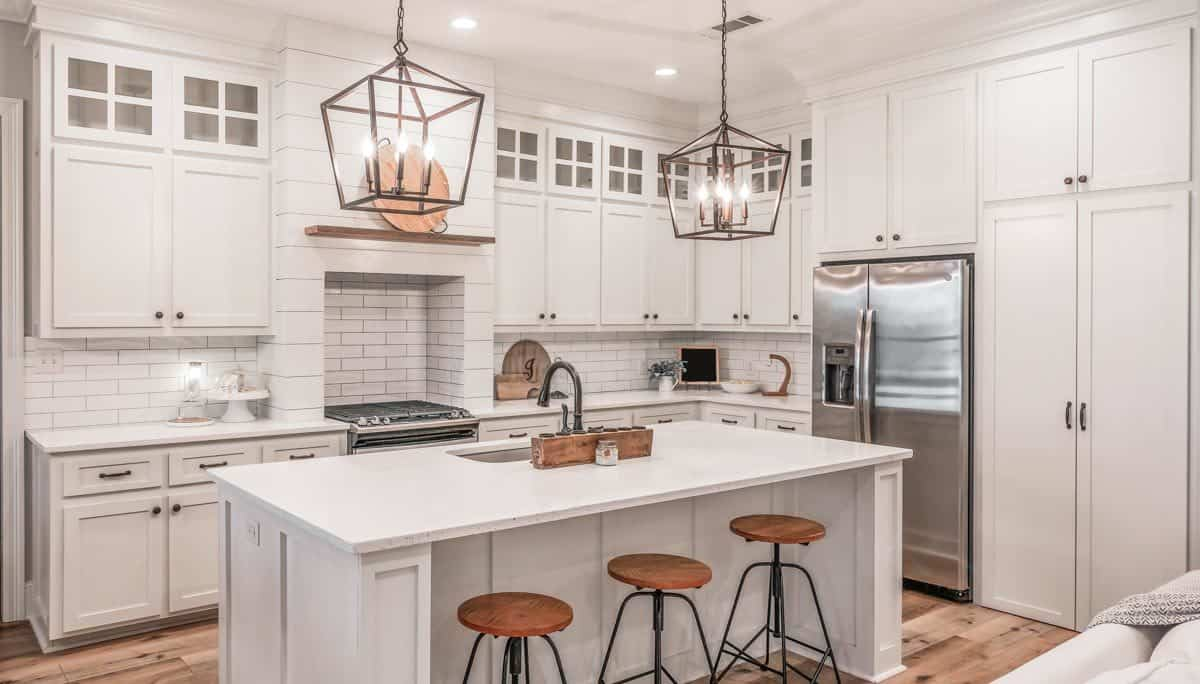 The kitchen is equipped with stainless steel appliances, white cabinetry, a prep island, and white subway tile backsplash.