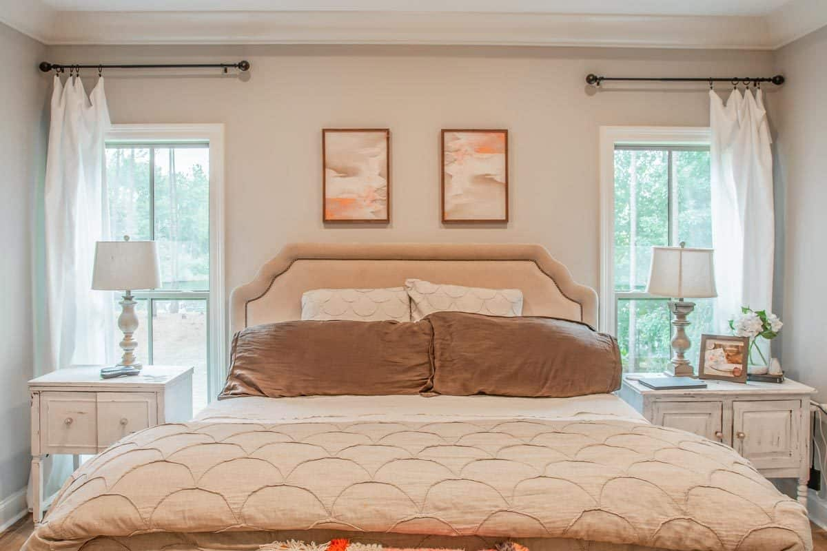 The primary bedroom has a tray ceiling and a beige upholstered bed with a bench at its end.