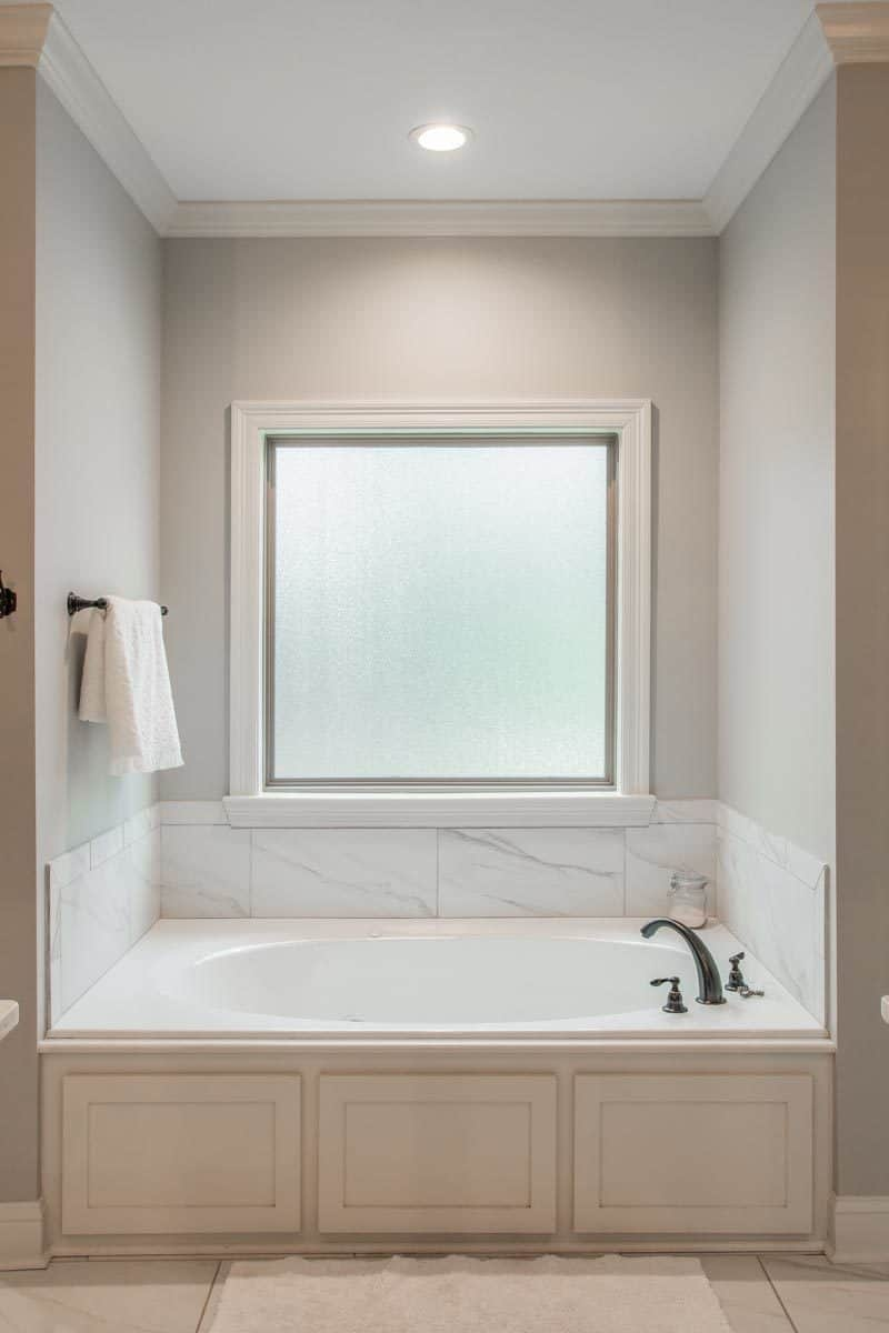 The drop-in bathtub with iron fixtures is placed underneath the picture window.