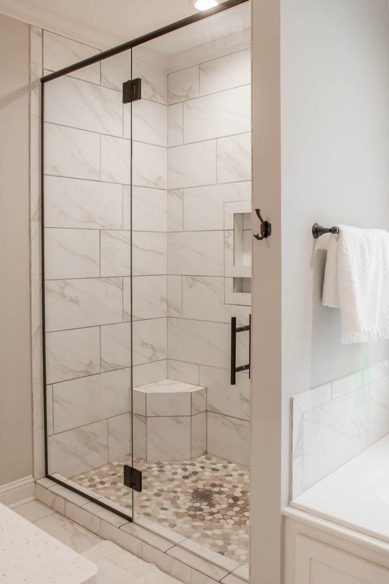 Walk-in shower with marble tiled walls, pebble flooring, inset shelves, and a corner built-in seat.