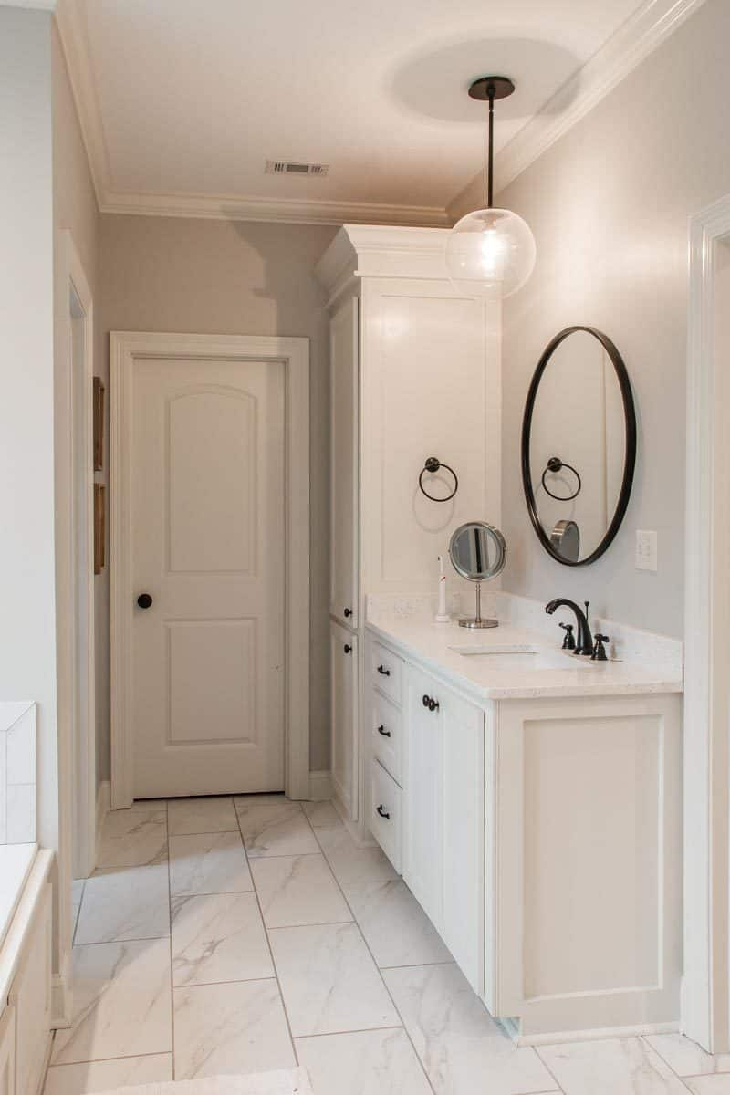 A full-length mirror complements the white vanity that's fitted with wrought iron fixtures.