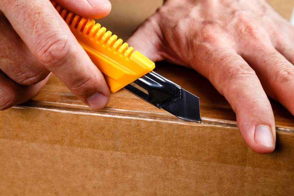 A cardboard box being cut open with the use of a utility knife.
