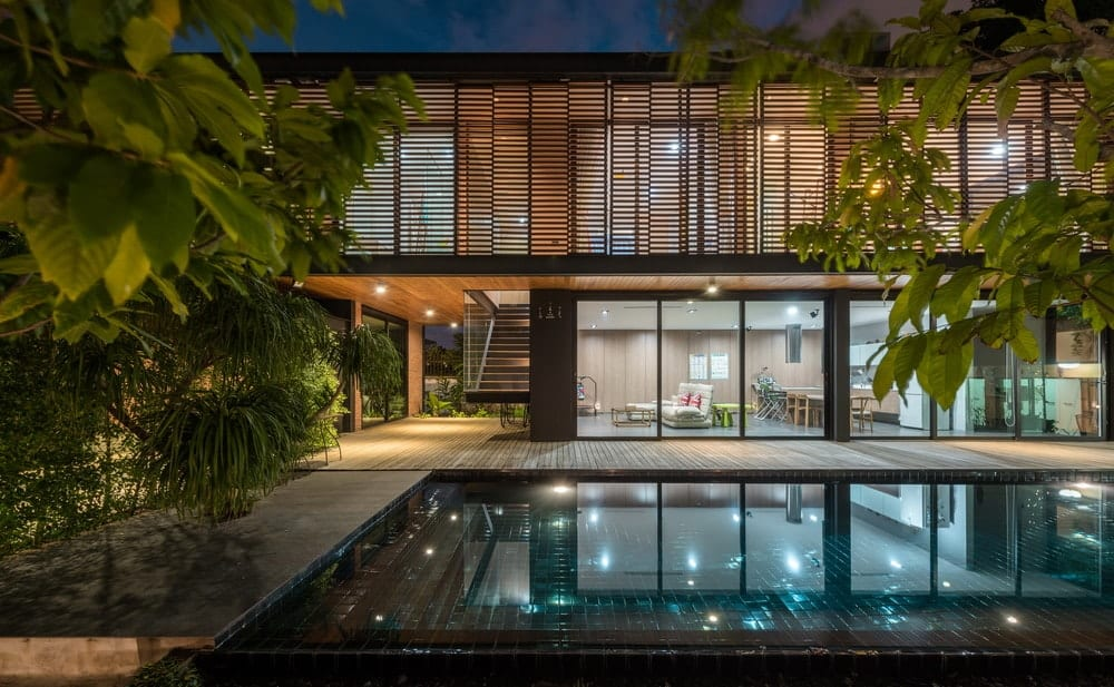 This is a look at the house during nighttime showcasing the warm glow of the interiors escaping through glass walls on the ground level and the wooden panels of the floor above that reflect on the pool.