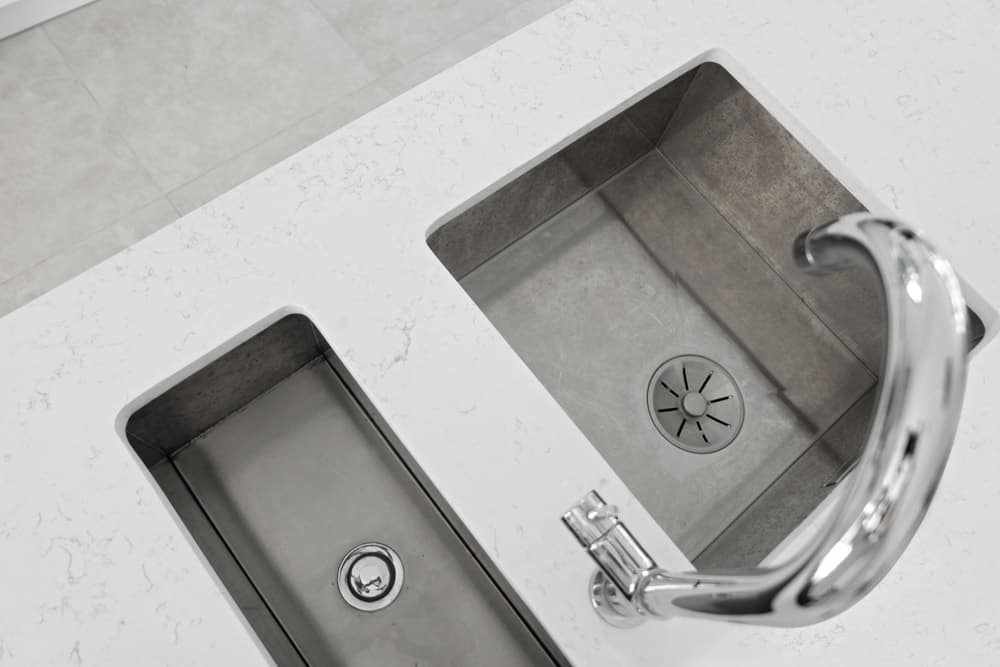 A top view of an under mount kitchen sink with a disposal unit beside it.