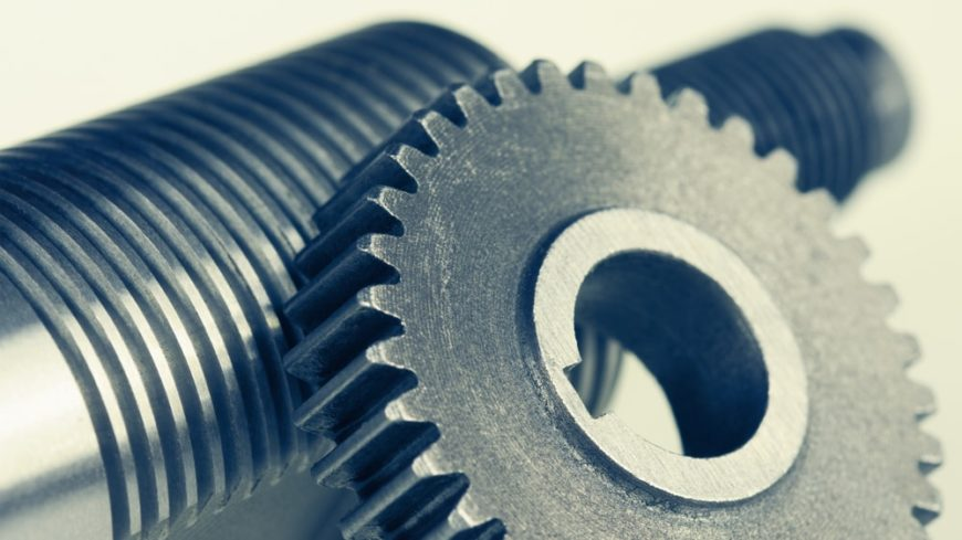 This is a close look at a cog wheel and a bolt with thread.