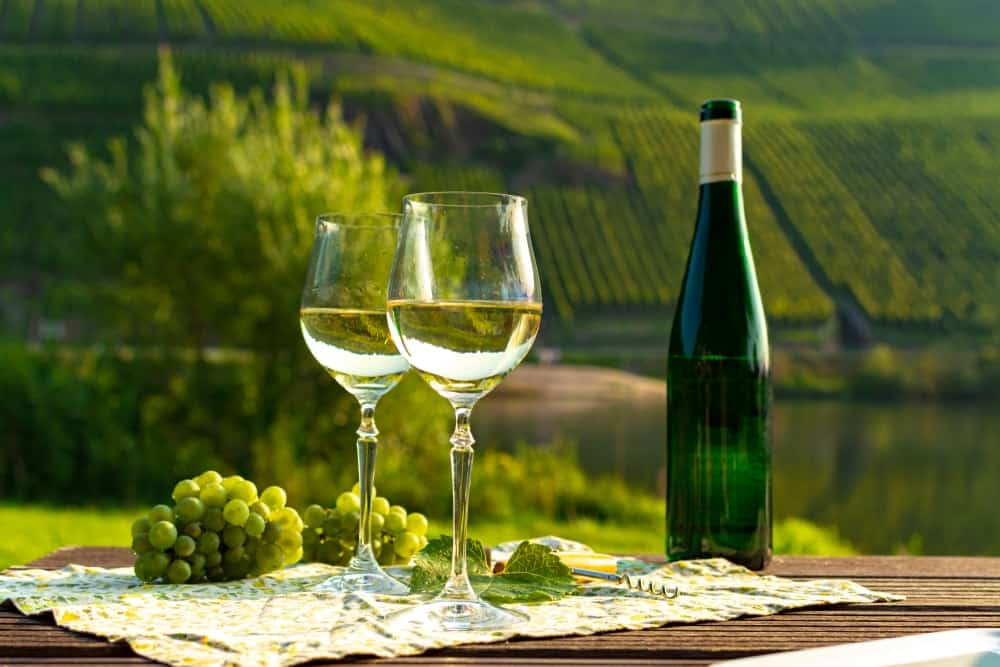 Clusters of Riesling grapes and wine on a wooden table overlooking the valley.