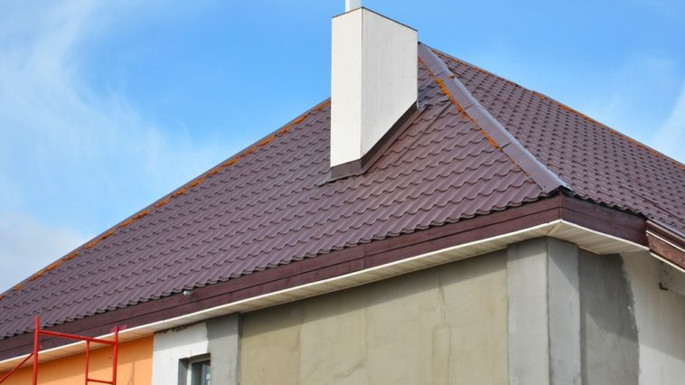 A close look at a dark red metal tiled bonnet roof with a white chimney.