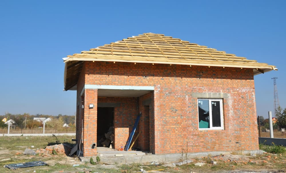 A small brick house with bonnet roof under construction.