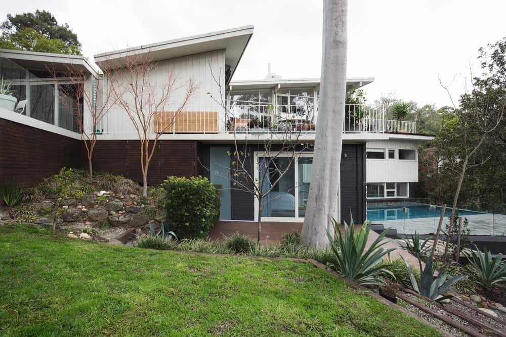 This is an exterior look at this house with a backyard pool, a balcony and butterfly roof.