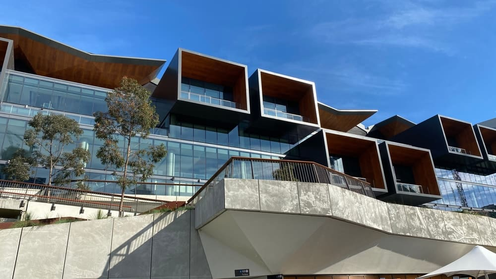 This is a close look at a modern building complex with glass walls, balconies and butterfly roofs.
