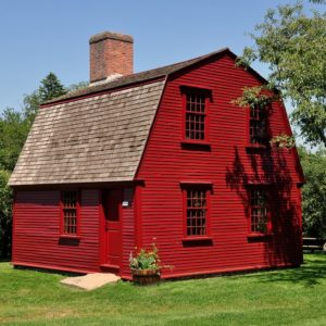 A cottage-style home with dark red exterior walls, a brick chimney and a gambrel roof.