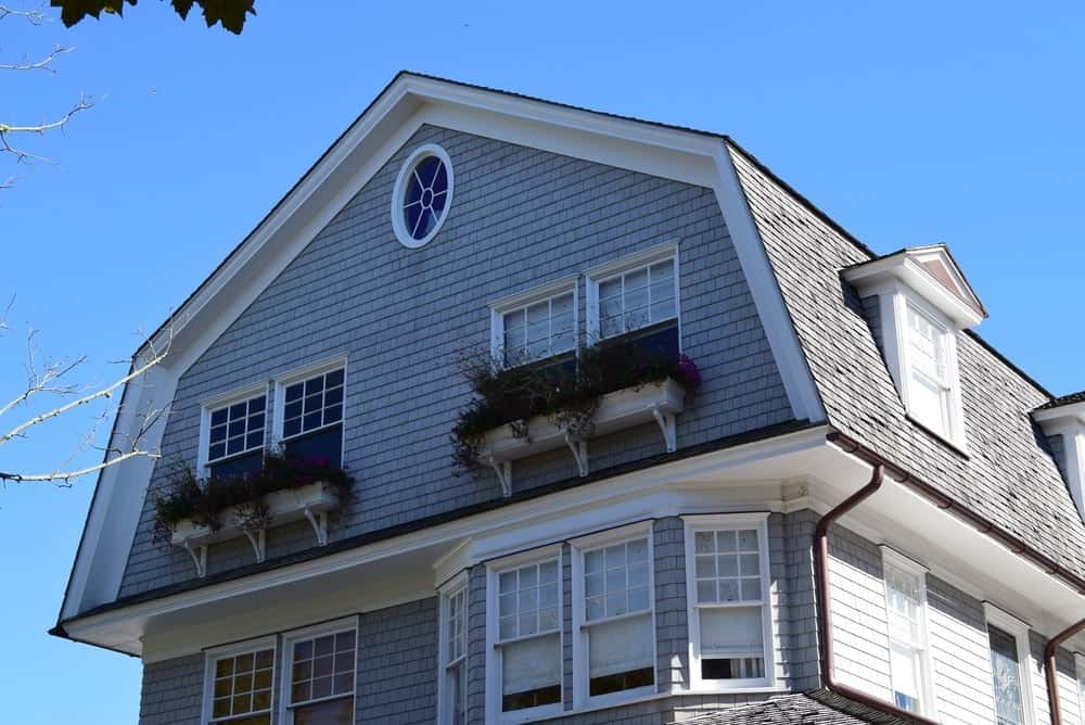 A close look at a traditional-style home with dormer windows and a gambrel roof.