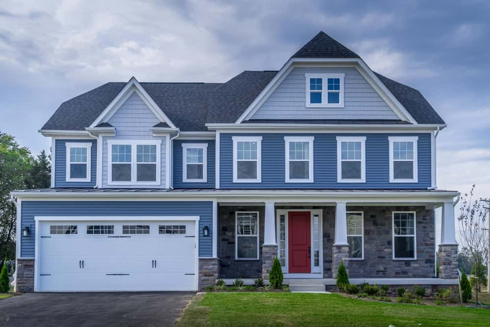 This is a front view of a house that has blue tones on its walls and jerkinhead roof.