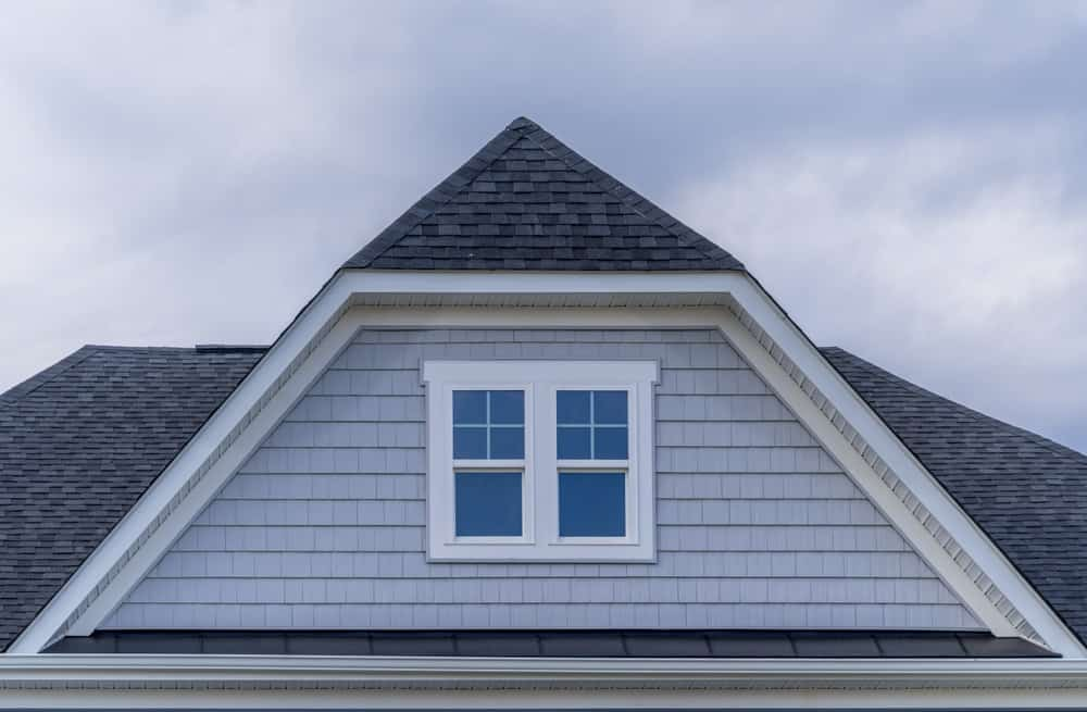 This is a close look at the roof of a house that has roof shingles on its jerkinhead roof.