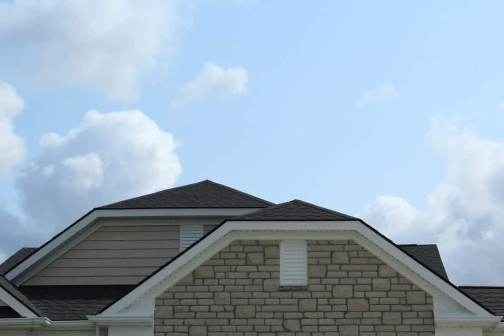 This close look at the roofs of a house showcases the jerkinhead roof design.