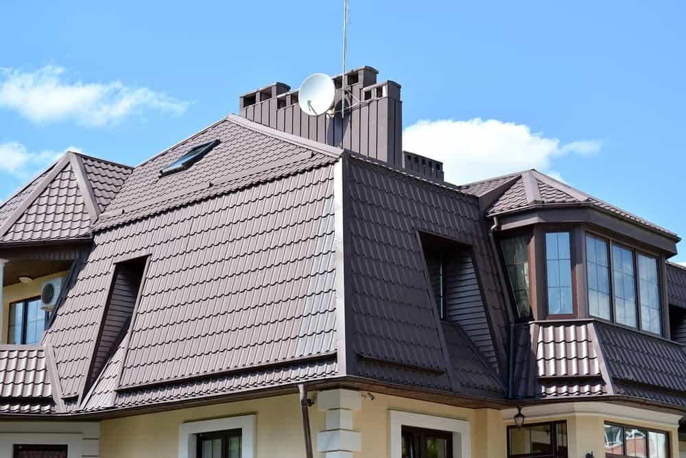 This is a close look at a house with dark metal tiles on its mansard roof.