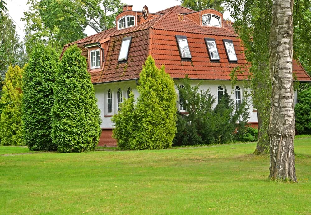 This is a house with red tiled mansard roof that is complemented by the lush landscaping.