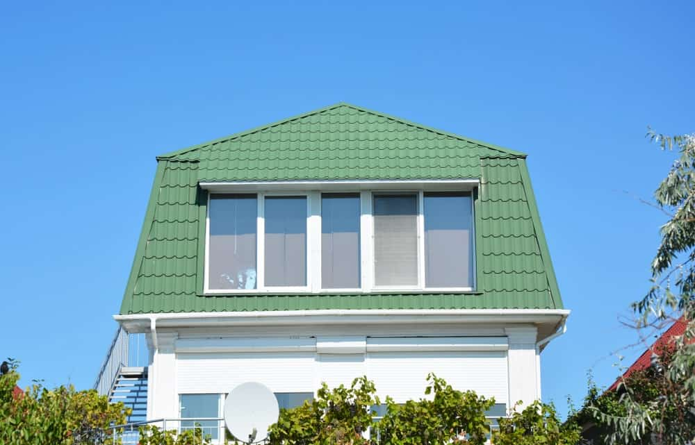 This is an exterior look at a green metal mansard roof.