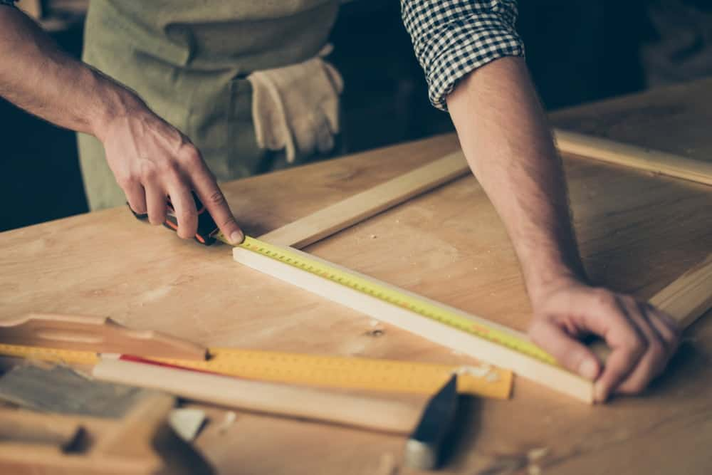 This is a close look at a carpenter measuring the wooden frame on his workshop table.