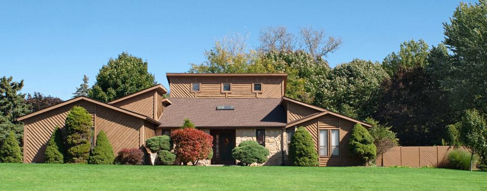 This is an exterior look at a brown wooden house with saltbox roof.
