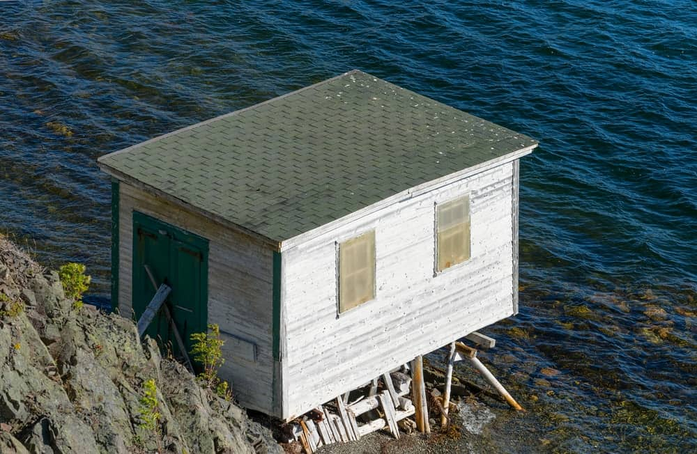 This is a wooden cottage with a shed box roof by the sea.