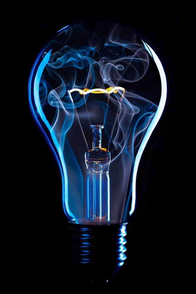This is a close look at a light bulb with glowing blue vapor inside.