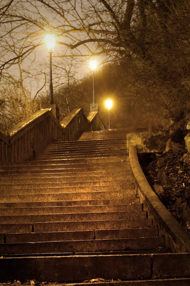 Stone steps at a park lit by the bright yellow lights of the lamp posts.
