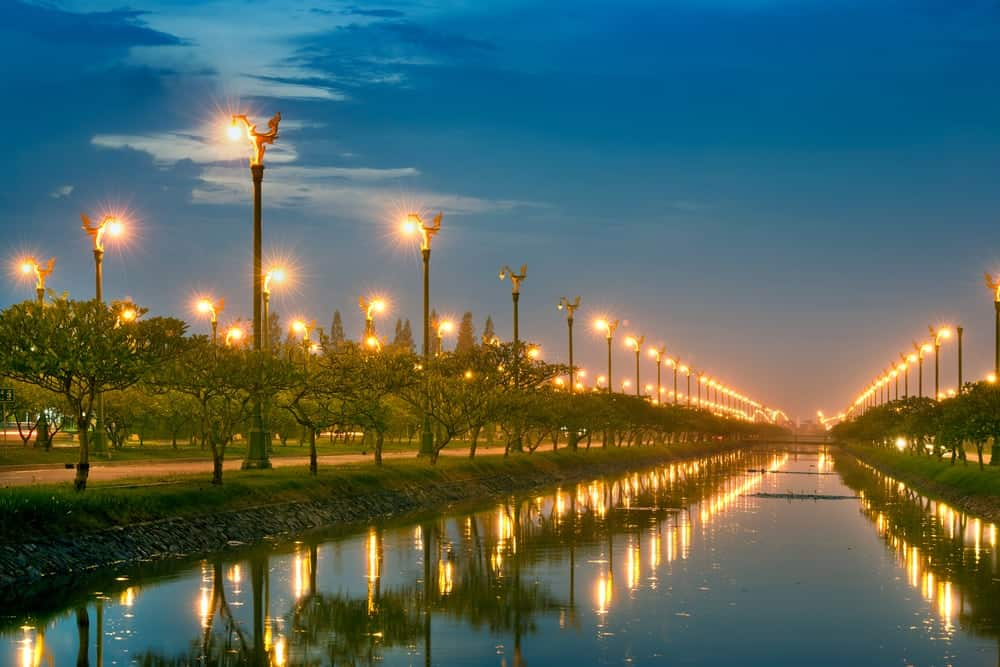 A massive park with a canal lit by the multiple rows of lamp posts with a warm glow.