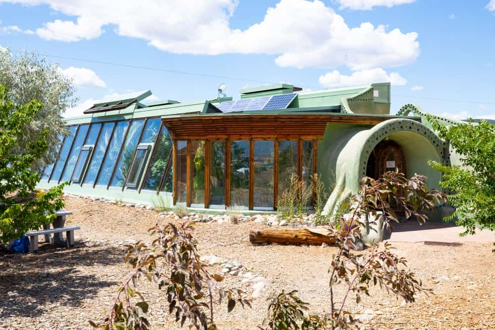 A front view of an earthship with a bright mint green accent to its glass walls.