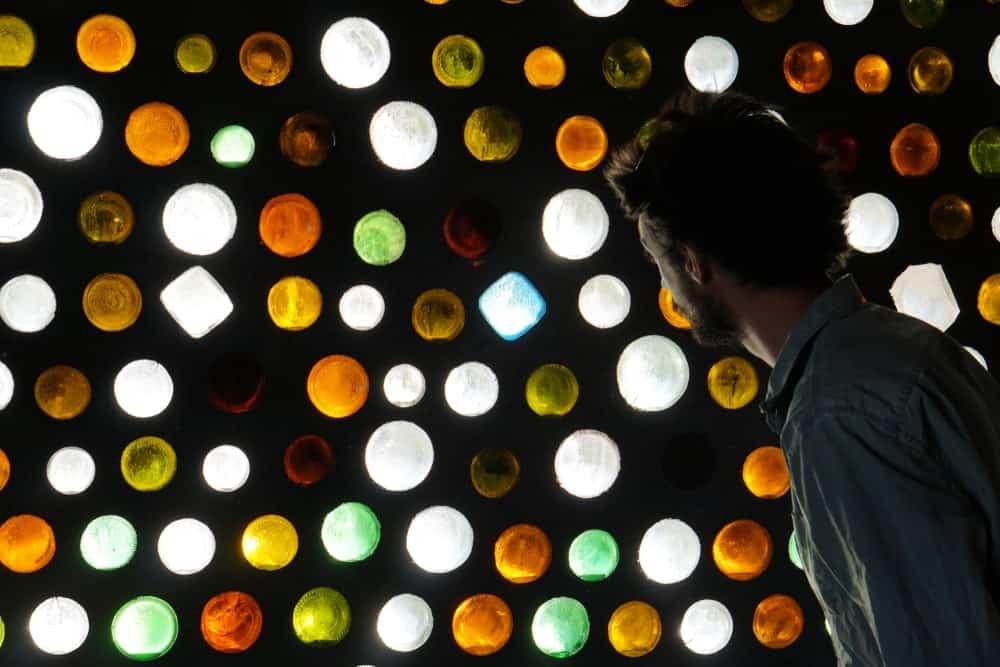 A man admiring an earthship wall made of glass bottles.