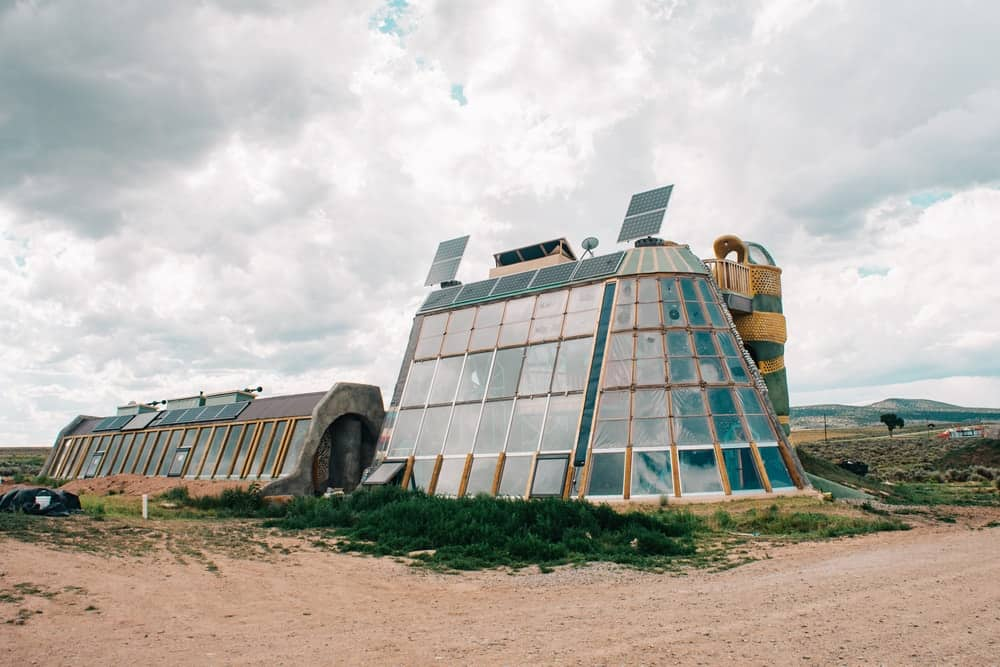 This is a rear view look at an earthship with glass walls and solar panels.