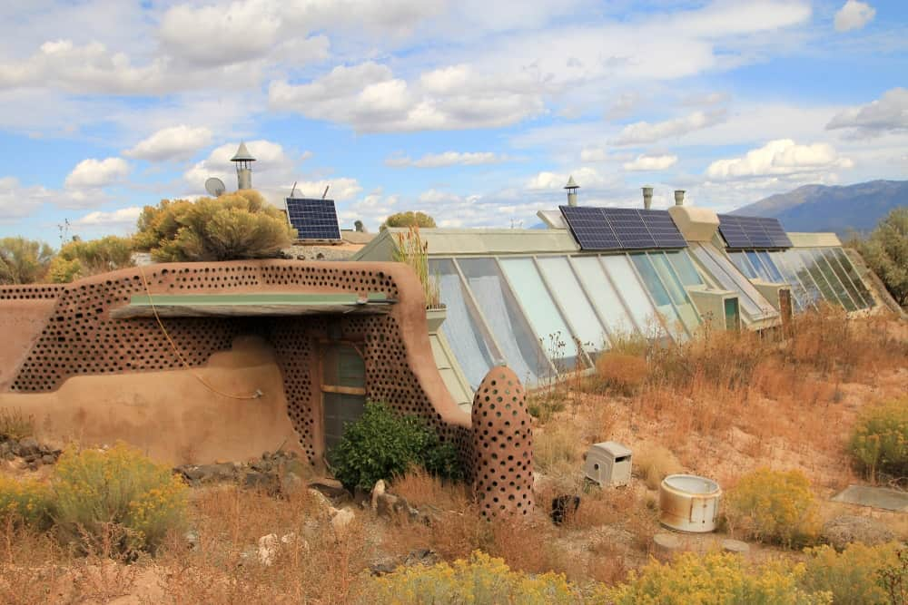 This is a look at an earthship featuring a front door surrounded by earthy materials and glass walls beyond.