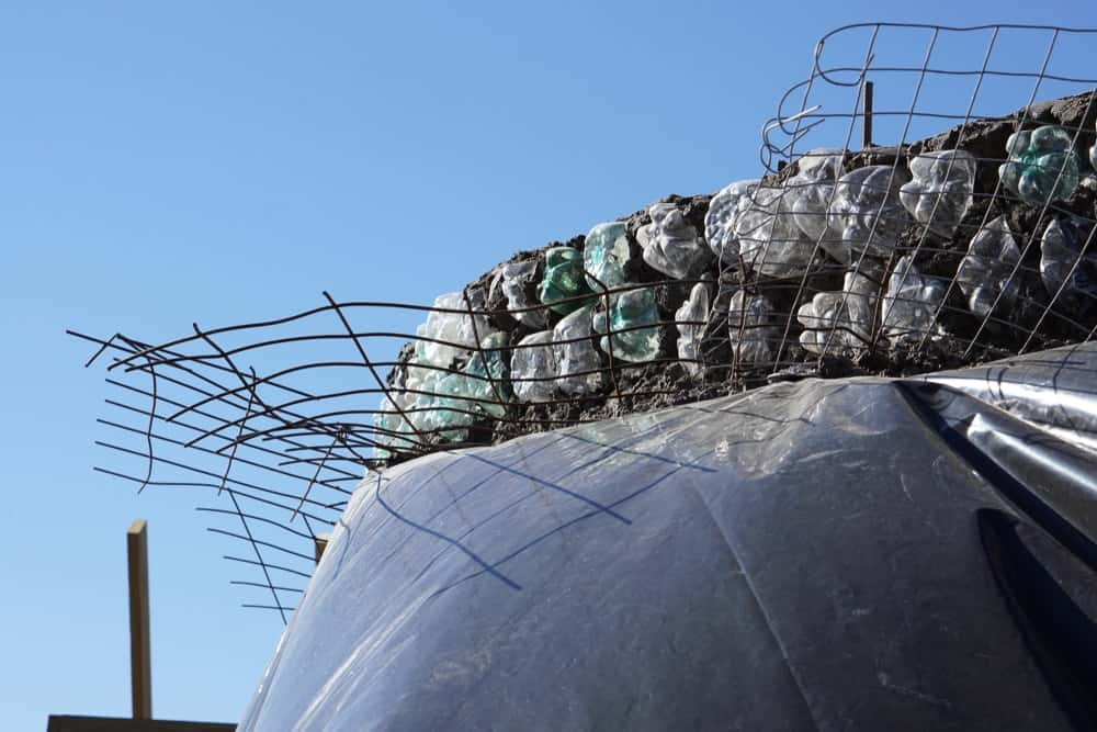 This is a close look at an earthship construction with bottles and cans used as bricks.