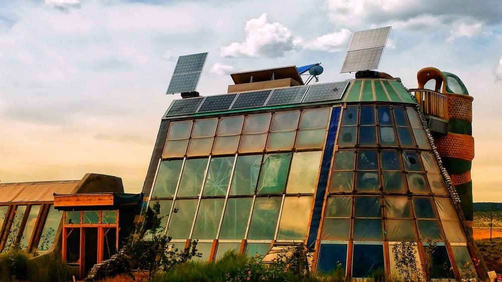 This is a close look at an earthship with large glass walls and solar panels.
